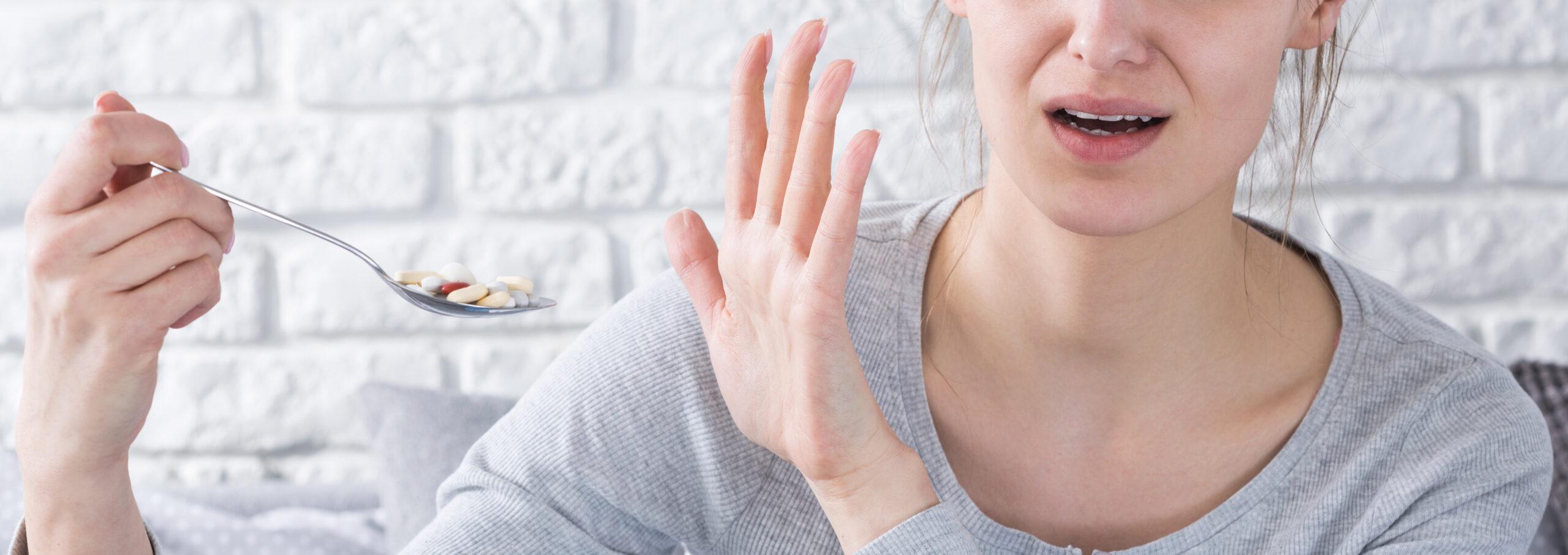 Vrouw trekt vies gezicht en weigert pillen op lepel in te nemen