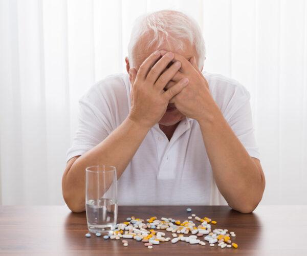 depressieve oude man aan tafel vol pillen