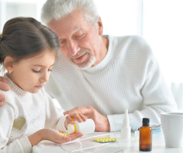 opa steunt kleindochter bij het nemen van haar pillen