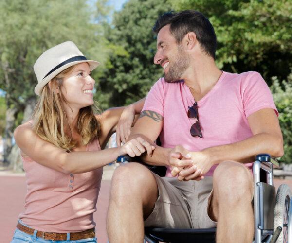 jonge man in rolstoel kijkt naar zijn mooie vrouw