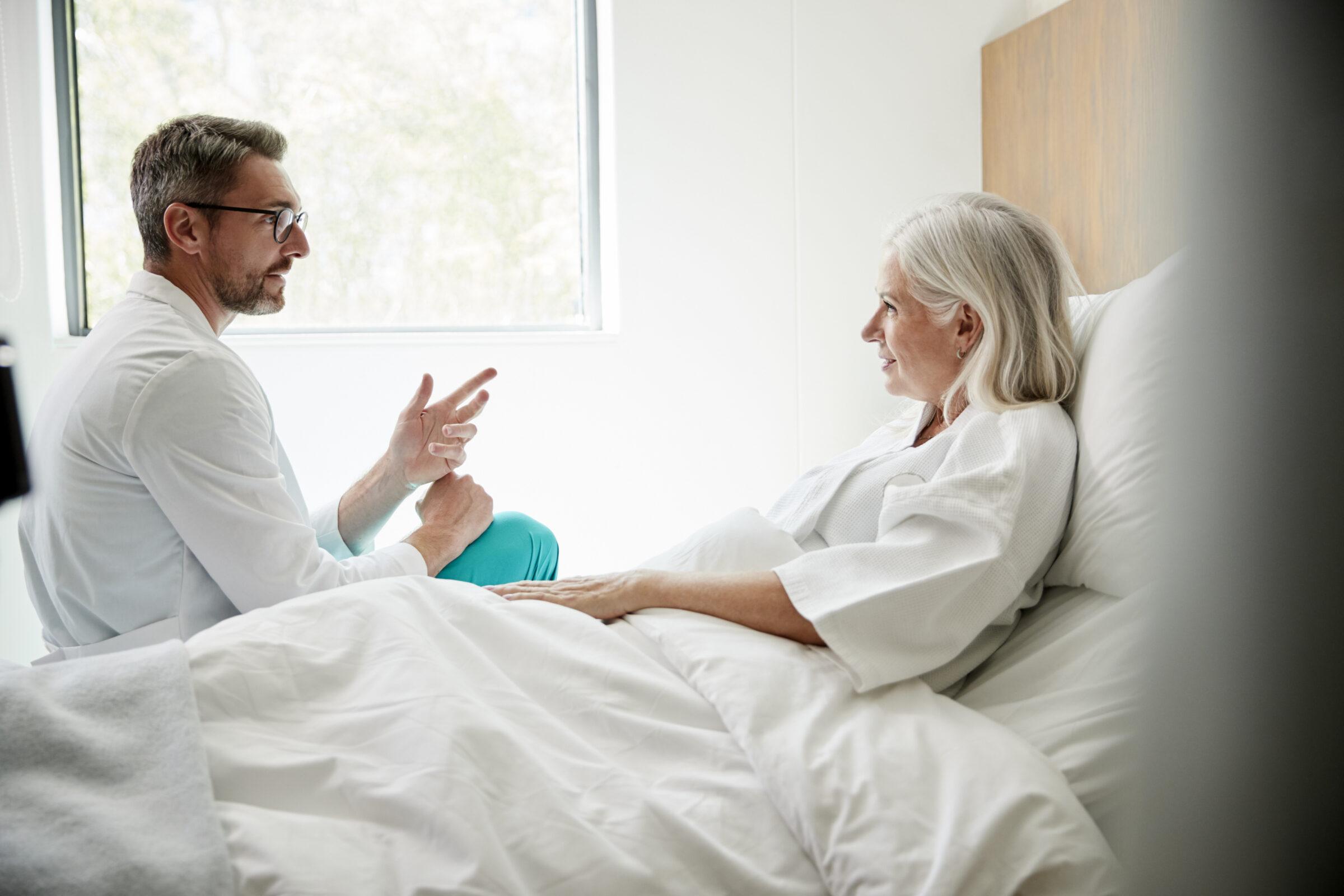 vrouwelijke patiënt in ziekenhuisbed heeft gesprek met dokter