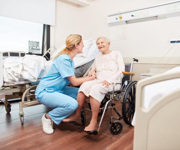 oude vrouw in rolstoel krijgt hulp van zuster