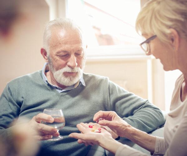 vrouw helpt oude man met pillen uitzoeken