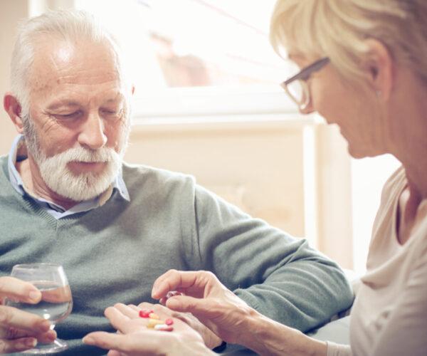 Vrouw helpt oudere man met het uitzoeken van zijn pillen