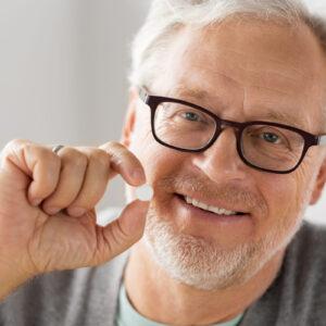 charismatische oude man laat paracetamol zien tussen duim en wijsvinger