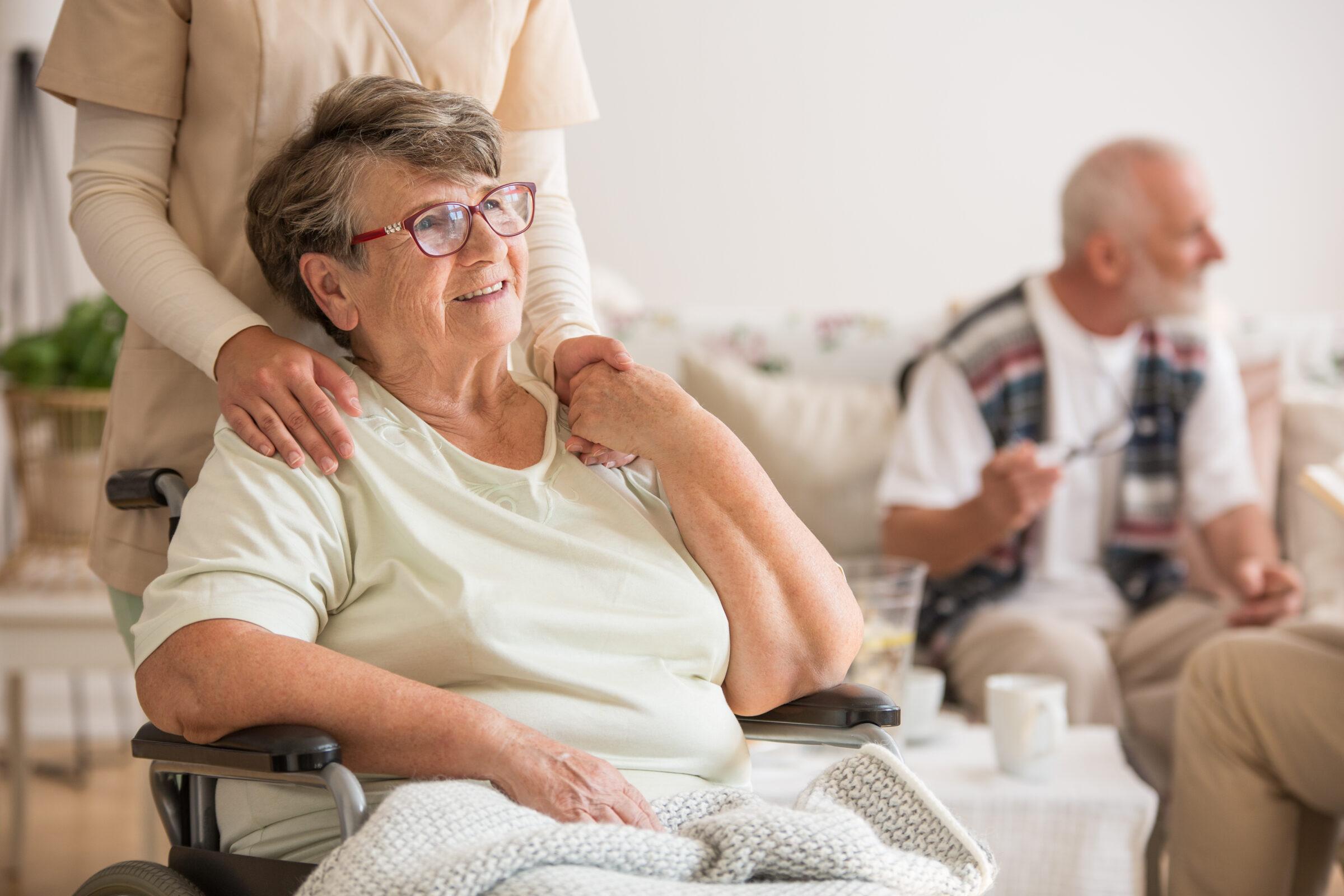 oude dame in rolstoel houdt hand van verpleegster vast