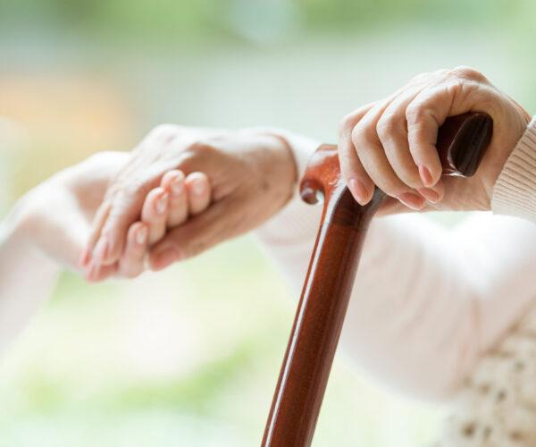 Hand van oude vrouw wordt vast gehouden