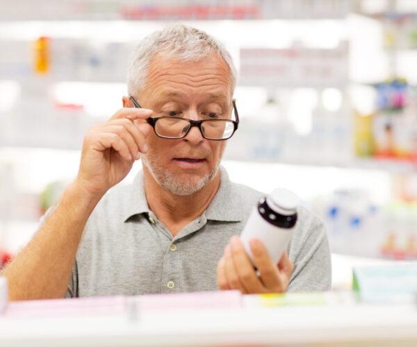 Man met leesbril in de apotheek leest verpakking van pot pillen